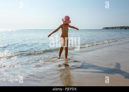 Junge Frau, unruhige Kinder in süßen Sommer Hut ist Tanzen und planschen im flachen Wasser, Sandstrand am Meer. - Stockfoto