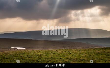 Sonnenstrahlen Sonnenlicht glänzen durch Schwere Regenwolken über eine moorlandschaft Landschaft Landschaft in Yorkshire, UK. - Stockfoto