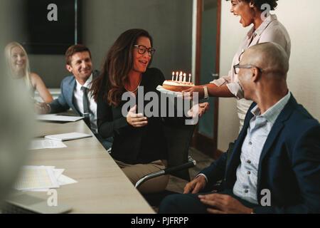 Afrikanische Frau, die eine Geburtstagstorte für weibliche Führungskraft im Konferenzraum. Arbeitnehmer feiern Geburtstag im Büro des Kollegen während einer Konferenz. Stockfoto