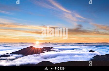 Eine flammende Morgen Sonne über eine Verkleidung von Wolken in den Krater des Haleakala, einem schlafenden Vulkan auf der Insel Maui, Hawaii - Stockfoto