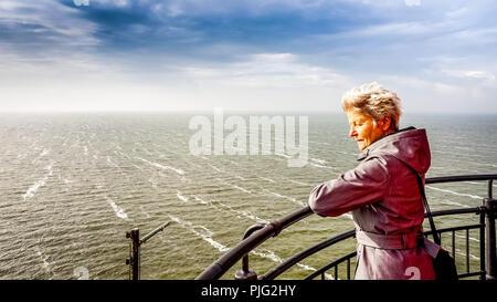 Ältere Frau beobachten das stürmische Wetter über het IJsselmeer vom Leuchtturm im historischen Fischerdorf Urk in den Niederlanden - Stockfoto