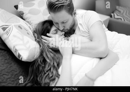Romantisches Paar in Liebe liegend auf Bett - Stockfoto