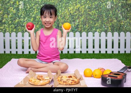 Asiatische chinesische Mädchen mit Picknick im Garten - Stockfoto