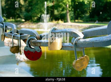 Symbolische liebe Vorhängeschlösser auf dem Geländer einer Brücke mit einem Brunnen in einem Park auf Hintergrund fixiert - Stockfoto