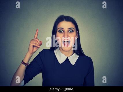 Porträt einer beiläufigen Frau mit Finger bis in helle Idee auf grauem Hintergrund - Stockfoto