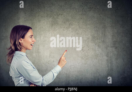 Seitenansicht der aufgeregten Frau mit Finger bis in helle Idee auf grauem Hintergrund - Stockfoto