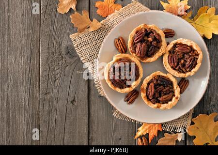 Platte von mini Pecan Pie Torten, rustikalen overhead Tabelle Szene auf einem Holz Hintergrund - Stockfoto