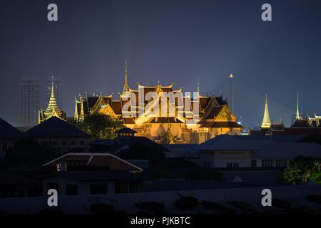 Lit Grand Palace in Bangkok, Thailand, gesehen über Gebäude am Abend. - Stockfoto
