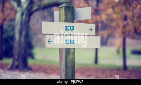 Wegweiser in einem Park mit Pfeilen, die zwei entgegengesetzten Richtungen hin zur EU und UK. - Stockfoto