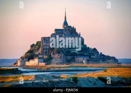 Sonnenuntergang am Mont Saint-Michel, Normandie, Frankreich. Mont Saint-Michel zählt zu den beeindruckenden Sehenswürdigkeiten Frankreichs. - Stockfoto