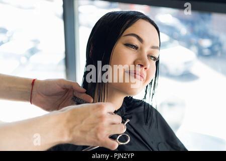 Glückliche junge Frau, die sich einen neuen Haarschnitt von Friseur im Salon - Stockfoto