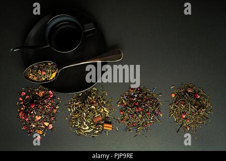 Trocken Tee und Kräuter Sammlung von verschiedenen Arten auf schwarz Tabelle - Stockfoto