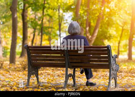 Ältere Frau sitzen auf einer Bank im Herbst Park. Einsam im Alter von Frau sitzt auf der Bank im Herbst Park an Bäumen sieht. - Stockfoto