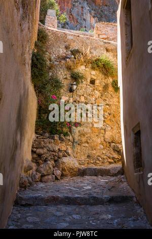 Traditionelles Dorf Gasse mit Steinmauern, die Blumen und die Lampen - Stockfoto