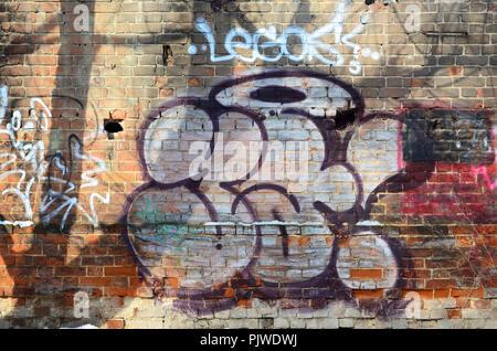 Die alte Mauer, in Farbe graffiti Zeichnung rot aerosol Farben gemalt. Hintergrundbild auf dem Thema der Zeichnung Graffiti und Street Art