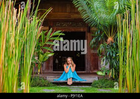 Attraktives Mädchen sitzen auf der Veranda des Bungalows, geniessen sie einen wunderschönen tropischen Garten. Junge Frau, die sich in Luxus Villa - Stockfoto
