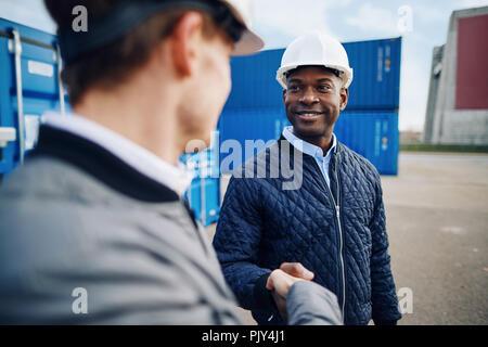 Zwei lächelnde Ingenieure hardhats durch den Versand von Containern auf einem kommerziellen dock Hände schütteln stehen zusammen tragen - Stockfoto