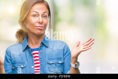 Mittleres Alter senior Hispanic Frau über isolierte Hintergrund ratlos und verwirrt Ausdruck mit den Armen und hob die Hand. Zweifel Konzept. - Stockfoto