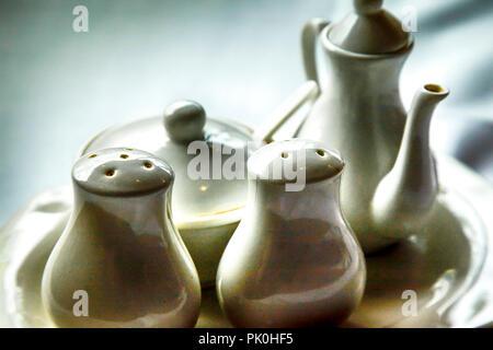 Nahaufnahme eines einfachen weißen Keramik Set creme & Zucker mit passenden Salz & Pfefferstreuer in einem beleuchteten Szene auf eine weiße Tischdecke auf dem Tisch gesetzt - Stockfoto