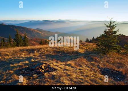 Spektakuläre Aussicht auf die Hügel von Smoky Mountain Range in violett grau Nebel; abgebrochene Steine des Campingplatzes Kamin unter blauen, wolkenlosen Himmel auf einer wa - Stockfoto