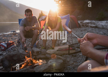 Gruppe von Freunden Heizung hot dog in der Nähe von Lagerfeuer - Stockfoto