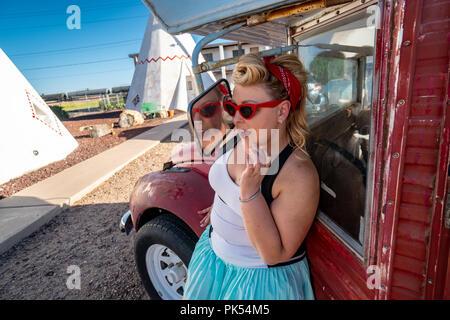 Blond erwachsenen Weibchen mit einem 1950er Jahrgang Pin up Frisur steht in der Nähe ein verlassenes Oldtimer, das Tragen von Cat eye Sonnenbrille - Stockfoto