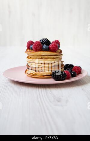 Pfannkuchen mit Beeren auf einem Rosa die Platte über der weißen Holz- Hintergrund, Seitenansicht. - Stockfoto