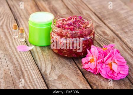 Jam jar, Gesichtscreme, Flasche ätherische Öl der Rosenblätter auf Holz- Hintergrund. - Stockfoto