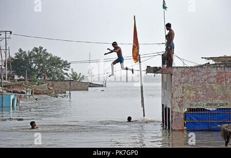 September 11, 2018 - Allahabad, Uttar Pradesh, Indien - Jugend stehen auf einem Tempel springen zu überfluteten Wasser des Flusses Ganga, nachdem der Wasserstand des Flusses Ganga rose Erstellen einer flut - wie Situation bei Daraganj. (Bild: © Prabhat Kumar Verma/ZUMA Draht) - Stockfoto