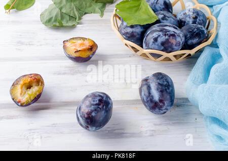Frisches Lila Pflaumen in einem korbwaren Vase, Pflaumen wird halbiert und die helle Fruchtfleisch leuchtet auf weißem Hintergrund Holz, kopieren, - Stockfoto