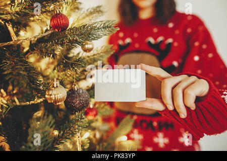 Hand mit Kreditkarte close-up auf dem Hintergrund der Goldenen schönen Christbaum mit Lichtern in festlichen Raum. Christmas shopping und Verkauf Konzept. d - Stockfoto