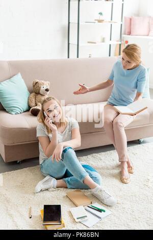 Mutter gezwungen, ihre Tochter zu untersuchen, während Sie sprechen über das Telefon - Stockfoto