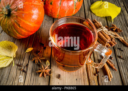 Pikante Kürbis Kaffee, Herbst hot drink Glas Schale, mit Kürbissen, Zimt und Gewürze auf alten rustikalen Holzmöbeln Background Copy space - Stockfoto