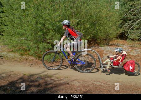Eine Lady Biker ihre Tochter Abschleppen in einem Weehoo kind Fahrradanhänger im Königreich Trails an der East Burke in Vermont, USA - Stockfoto