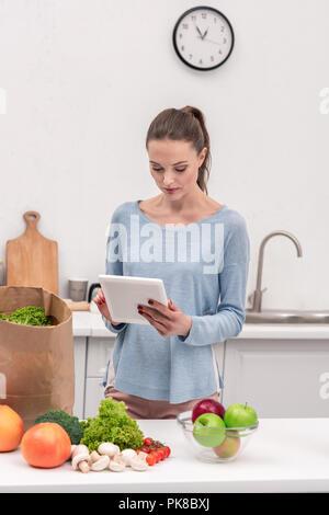 Attraktive Frau mit Tablet Prüfung Liste der kauft nach Einkaufen zu Hause - Stockfoto