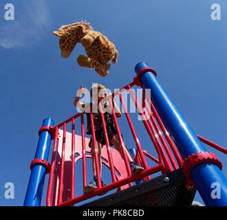 Ein sechs Jahre alter Junge spielen werfen Kuscheltiere Spielzeug an der Kamera - Stockfoto