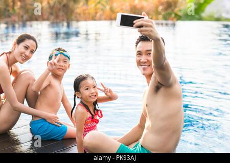 Glückliche Familie selfie mit Smart Phone am Pool - Stockfoto