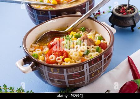 Suppe mit kleinen Nudeln, Gemüse und Fleisch in Schale auf der blauen Tabelle. Italienisches Essen. - Stockfoto
