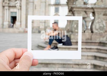 Nahaufnahme eines jungen kaukasischen Mann mit einem Karton weißen Rahmen in der Hand, für die Simulation eines Instant Foto, Framing ein junger Mann rast vor t - Stockfoto