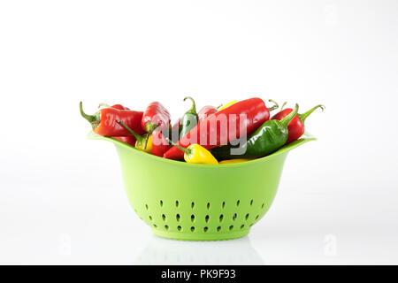 Capsicum annuum. Chilis in einer grünen Sieb. - Stockfoto