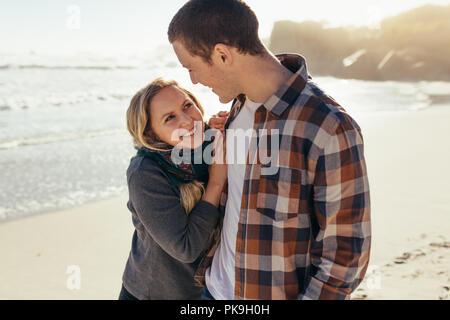 Liebespaar stehend draußen am Strand. Kaukasische Frau an ihrem Freund suchen und lächelnd an der Küste. - Stockfoto