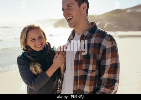 Schöner Mann zu Fuß mit seiner Freundin am Strand. Fröhlicher junger Paare zusammen entlang der Küste. - Stockfoto