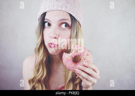 Portrait einer jungen und lustige blonde Frau isst eine rosa Donut - Stockfoto