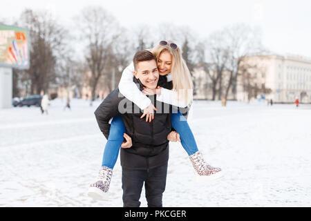 Junges Paar, durch die Stadt zu gehen. Der Kerl trägt das Mädchen auf den Rücken. - Stockfoto