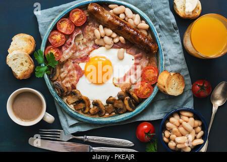 Ein traditionelles, englisches Frühstück. Spiegelei mit Würstchen, Pilze, Bohnen, Tomaten und Speck. Blick von oben.