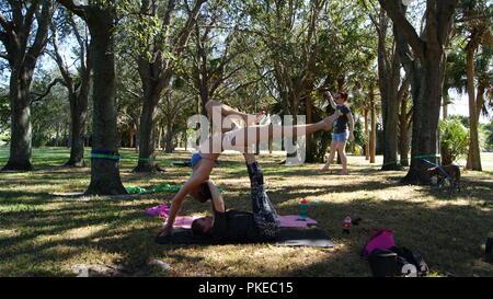 Junge Frauen, die das Üben acro Yoga in einem öffentlichen Park in Florida, Jupiter, Florida. USA - Juni 17., 2017. - Stockfoto
