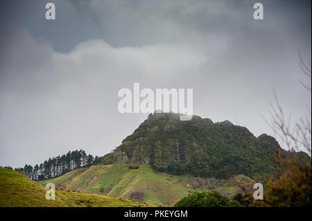 Ländliche Szene auf der Coromandel Halbinsel, Neuseeland. Grüne Hügel, bewaldete Hänge, dunklen stürmischen Himmel - Stockfoto