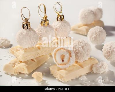 Runde Kleine blassgelbe Süßigkeiten in Kokos Späne in Form von Weihnachten Spielzeug mit goldenen Caps sind auf weiße Schokolade bars - Stockfoto