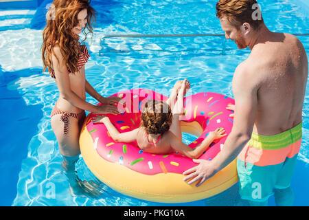 Lächelnden jungen Eltern spielt mit Tochter, während Sie schwimmen in einem Ring aus Gummi am Schwimmbad - Stockfoto