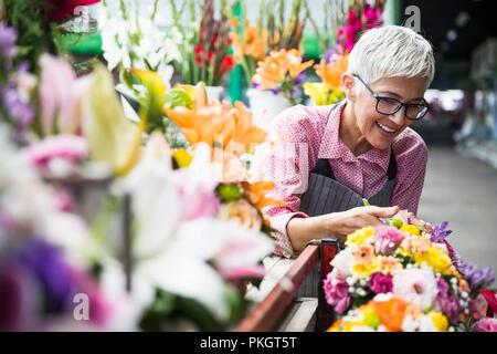 Charrming senior Frau arrangiert Blumen auf dem lokalen Markt - Stockfoto